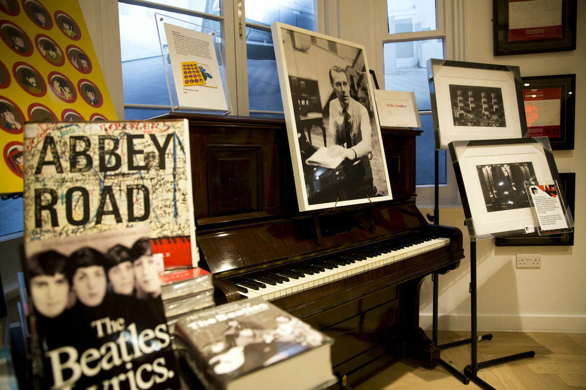 An image of George Martin, the Beatles' producer, is displayed in memory of him in the Abbey Road shop by the studios where the Beatles recorded albums and where the zebra crossing cover picture of the Abbey Road album was originally taken, in London, Wednesday, March 9, 2016. George Martin, the Beatles' urbane producer who quietly guided the band's swift, historic transformation from rowdy club act to musical and cultural revolutionaries, has died, his management said Wednesday March 9, 2016. He was 90. (AP Photo/Matt Dunham)