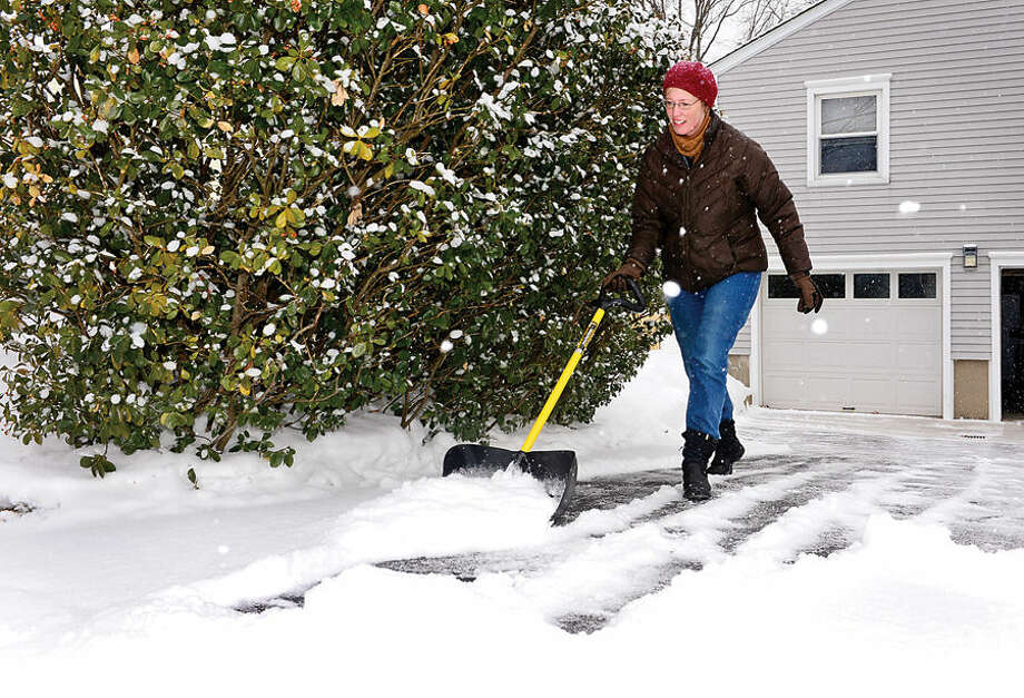 Hour photo / Erik Trautmann Norwalk resident Michelle Novak deals with the early morning snowfall at her home on Heather Lane Tuesday