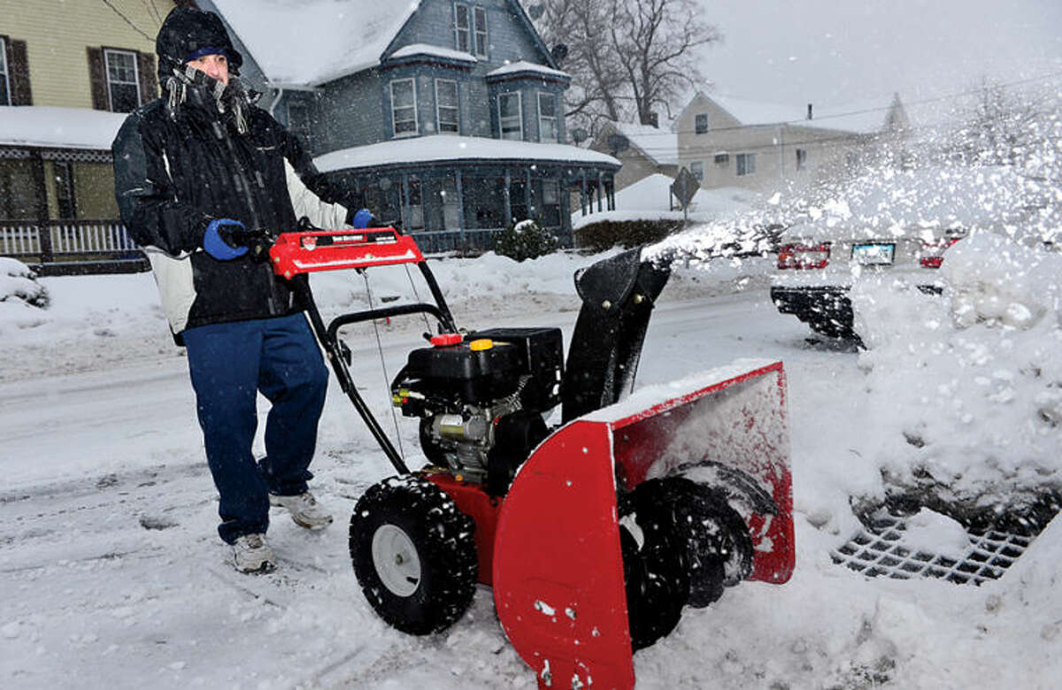 Hour photo / Erik Trautmann Norwalk resident Antonio Migliaccio clears the sidewalks in front of his residents as snow accumulations reach an inch Thursday monring.