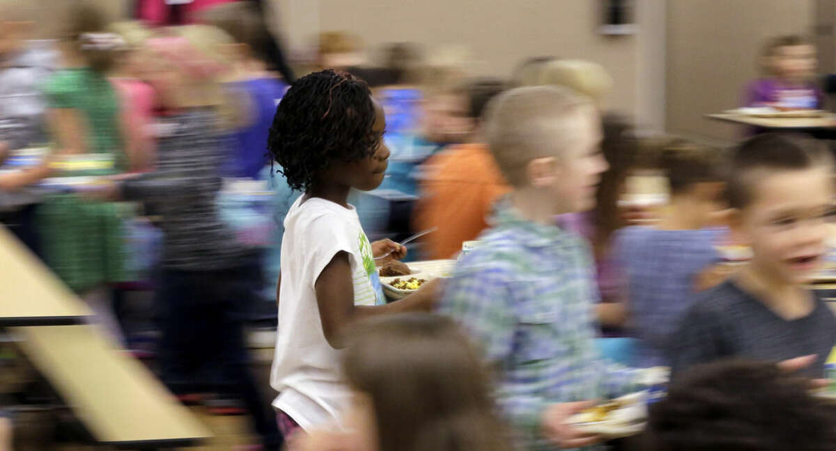 ADVANCE FOR USE WEDNESDAY, FEB. 18, 2014 AND THEREAFTER - In this Wednesday, Dec. 17, 2014 photo, Watford City Elementary School students dine in the cafeteria in Watford City, N.D. The booming population from the oil industry has brought diversity to a school that until recently had virtually none. (AP Photo/Eric Gay)