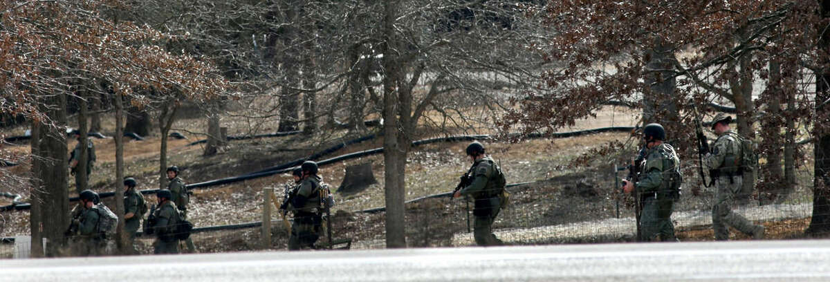 Police walk near a house where a man was found murdered on Tuesday, March 8, 2016, near New Florence, Mo. (Cristina Fletes/St. Louis Post-Dispatch via AP) EDWARDSVILLE INTELLIGENCER OUT; THE ALTON TELEGRAPH OUT; MANDATORY CREDIT