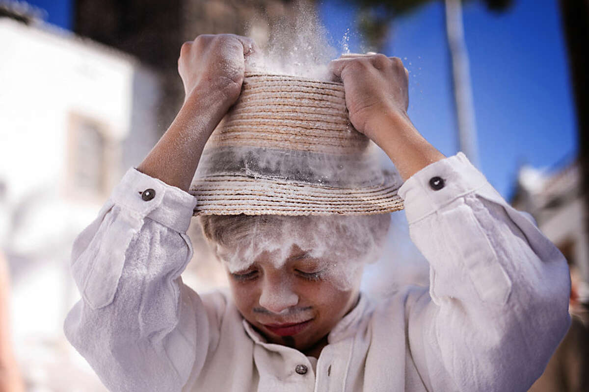 In this photo taken Monday, Feb. 16, 2015, a reveller known as 'Los Indianos' throws talcum powder on himself during a carnival in Santa Cruz de la Palma in the Canary Islands, Spain. 'Los Indianos' represent the return of emigrants from the Americas, who returned to the island wealthier. (AP Photo/Andres Gutierrez)