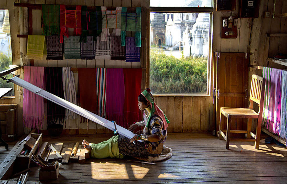 An ethnic Kayan-Padaung woman in traditional attire weaves at a souvenir shop in Ywama village, Inle Lake, northeastern Shan state, Myanmar, Monday, Feb. 16, 2015. Wearing neck-rings is officially discouraged in Myanmar but shop owners employ Padang women in traditional attire as a tourist attraction. (AP Photo/Gemunu Amarasinghe)