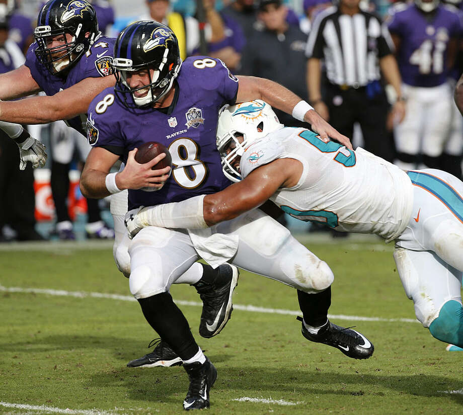 FILE - In this Dec. 6, 2015, file photo, Baltimore Ravens quarterback Matt Schaub (8) is sacked by Miami Dolphins defensive end Olivier Vernon (50), during the second half of an NFL football game, in Miami Gardens, Fla. Defensive end Olivier Vernon's transition tag has been removed by the Dolphins, allowing him to become a free agent hours after the team signed Mario Williams as a replacement. The transition tag was for $12.734 million, but the Dolphins withdrew the offer Wednesday, March 9, 2016, making it likely Vernon will depart after four seasons in Miami. (AP Photo/Wilfredo Lee, File)