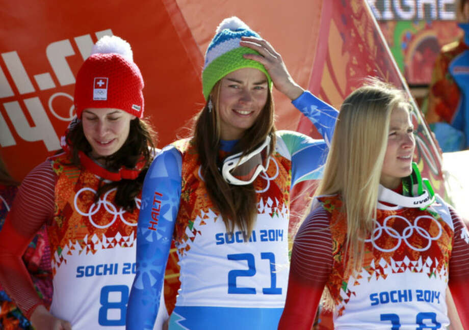 Women's downhill gold medalists Switzerland's Dominique Gisin, left, and Slovenia's Tina Maze, center, stand with bronze medalist Switzerland's Lara Gut before a flower ceremony at the Sochi 2014 Winter Olympics, Wednesday, Feb. 12, 2014, in Krasnaya Polyana, Russia. (AP Photo/Gero Breloer)