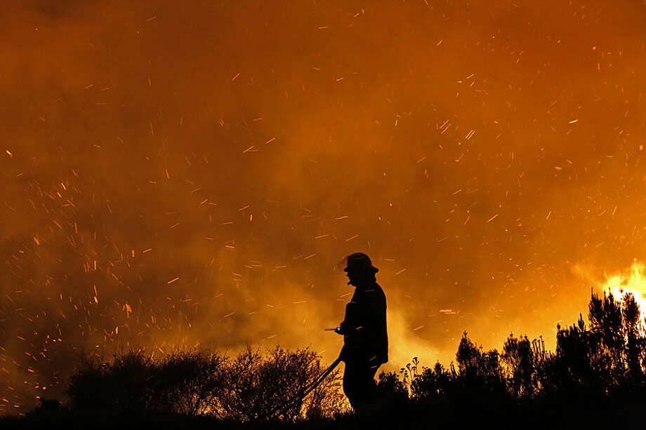 A fire fighter fights a fire on the lower part of Table Mountain near a residential area in Cape Town, South Africa, Monday, Feb. 16, 2015. The wildfire broke out near to Cape Town's central business district. (AP Photo/Schalk van Zuydam)