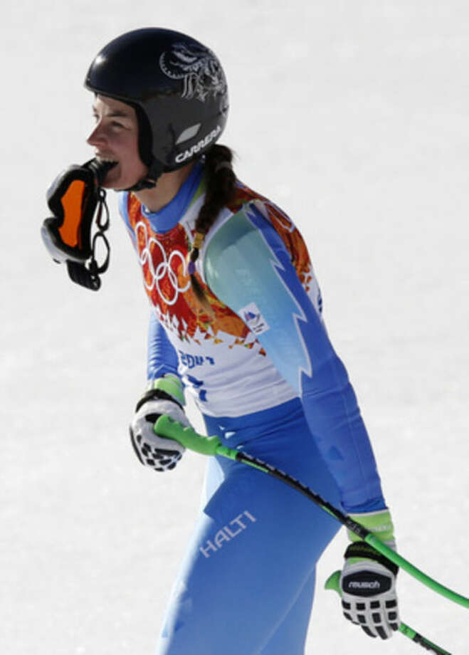 Slovenia's Tina Maze holds her goggles with her teeth after finishing the women's downhill to tie with Switzerland's Dominique Gisin to tie for the gold medal at the Sochi 2014 Winter Olympics, Wednesday, Feb. 12, 2014, in Krasnaya Polyana, Russia. (AP Photo/Christophe Ena)