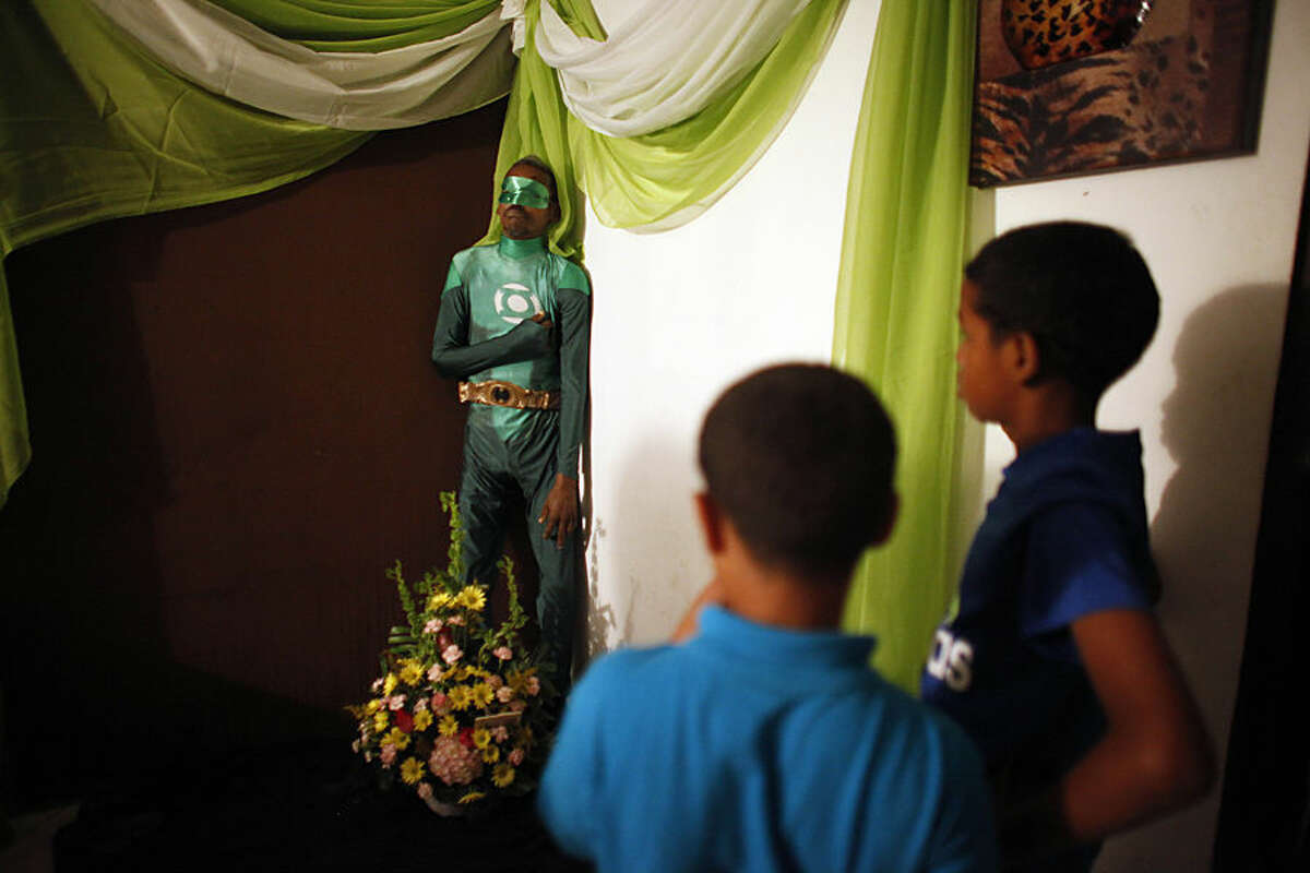 Two boys attend the wake of Renato Garcia, dressed as fictional superhero the Green Lantern and propped up against a wall in his sister's apartment, in San Juan, Puerto Rico, Sunday, Feb. 15, 2015. Garcia's sister explained that she and her brother never discussed funeral wishes, but neighbors and friends suggested dressing him as the comic book superhero. Weeks earlier Garcia had found the costume in a bag of donated clothing and started wearing the guise daily. Garcia, who was 50, died Monday of undetermined causes. (AP Photo/Ricardo Arduengo)