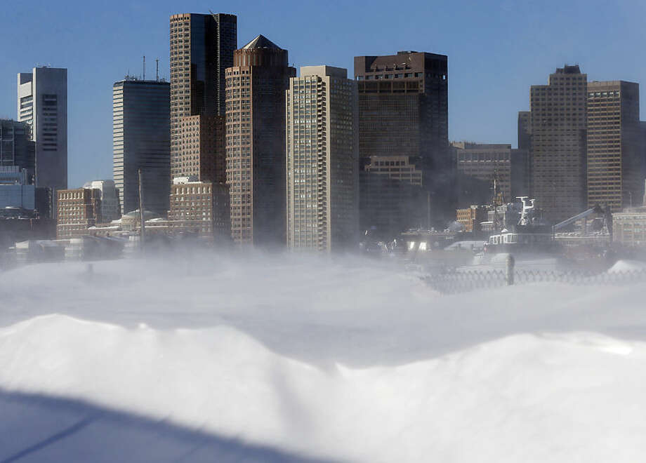 Blowing snow on the waterfront in the East Boston neighborhood of Boston partially obscures the skyline, Monday, Feb. 16, 2015. New England remained bitterly cold Monday after the region's fourth winter storm in a month blew through. (AP Photo/Michael Dwyer)