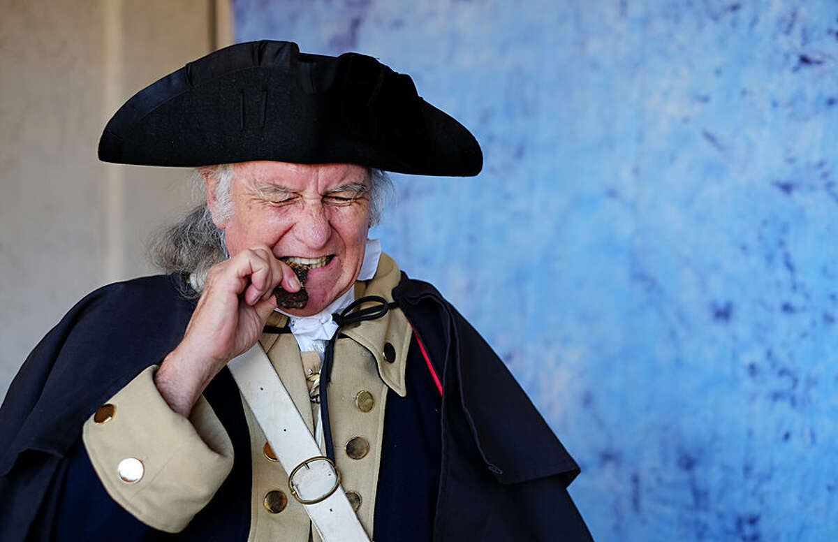 Presidential re-enactor C. Roger Cooper, portraying George Washington, takes a bite of jerky while waiting to take photos with visitors during President's Day celebrations at the Reagan Presidential Library in Simi Valley, Calif., on Monday, Feb. 16, 2015. (AP Photo/Richard Vogel)