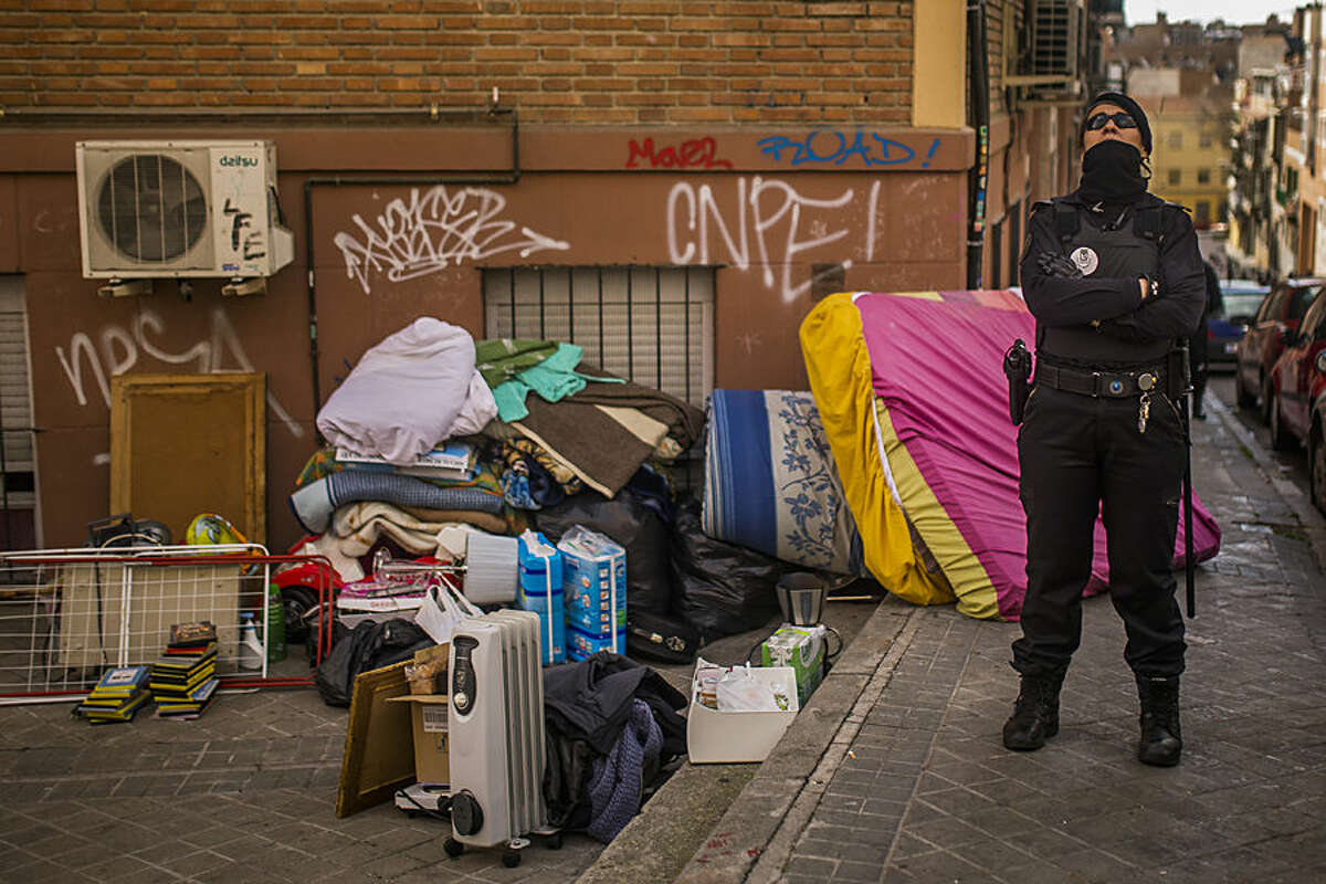 Rosario Echevarria Pedrezuela's furniture lies outside her apartment as police cordon the area during her and her family's eviction in Madrid, Spain, Monday, Feb. 16, 2015. The family occupied the foreclosed apartment ten months ago after they were evicted from their previous home. With both Echevarria Pedrezuela and her husband being unemployed and the family's sole income being a state benefit of euro 530 ($ 604), they could not afford to pay rent. Attempts to negotiate a lower rent with the bank were turned down, resulting in the family's eviction by police. (AP Photo/Andres Kudacki)