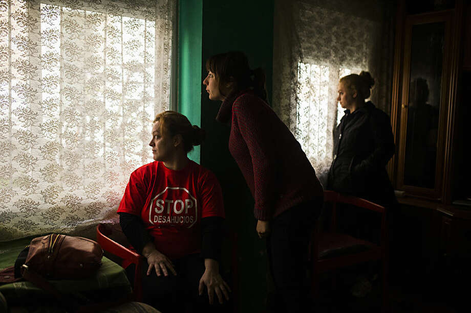 Rosario Echevarria Pedrezuela, left, her sister, right, and a housing rights activist, centre, watch as the police cordon the area around the apartment to evict her in Madrid, Spain, Monday, Feb. 16, 2015. The apartment occupied by Echevarria Pedrezuela, her husband Angel Echevarria Gabarri, 35, and their two children, aged 5 and 8 belongs to Bankia bank, after the previous owner was unable to continue paying the mortgage. The family occupied the foreclosed apartment ten months ago after they were evicted from their previous home. With both Echevarria Pedrezuela and her husband being unemployed and the family's sole income being a state benefit of euro 530 ($ 604), they could not afford to pay rent. Attempts to negotiate a lower rent with the bank were turned down, resulting in the family's eviction by police. (AP Photo/Andres Kudacki)