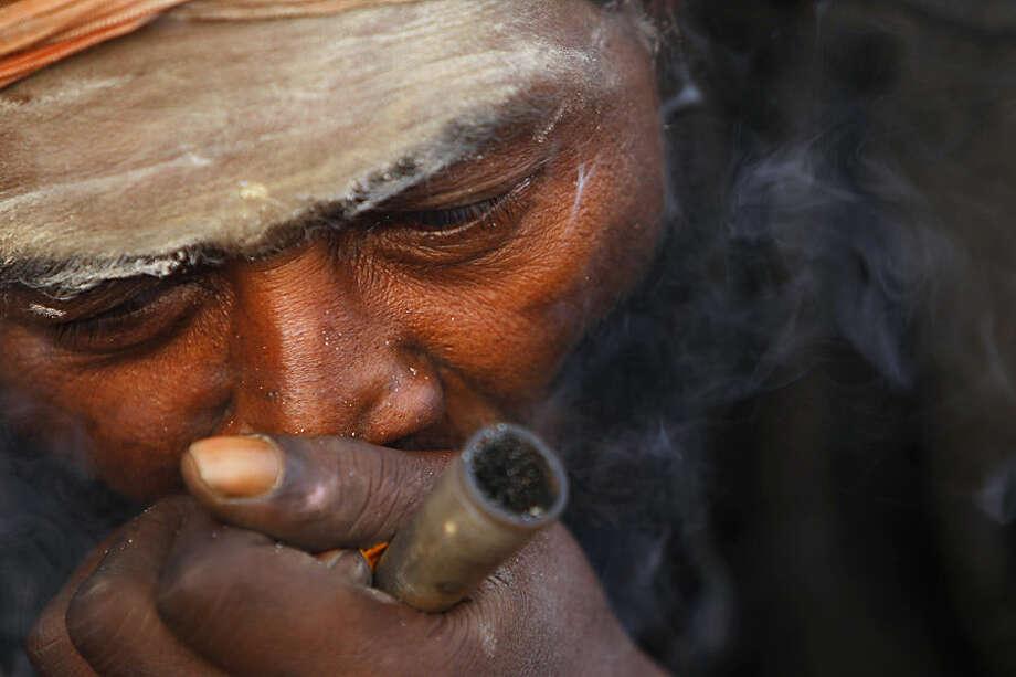 A Hindu holy man smokes marijuana at the courtyard of the Pashupatinath temple during Shivratri festival in Kathmandu, Nepal, Tuesday, Feb. 17, 2015. Shivratri, or the night of Shiva, is dedicated to the worship of Lord Shiva, the Hindu god of destruction. (AP Photo/Niranjan Shrestha)
