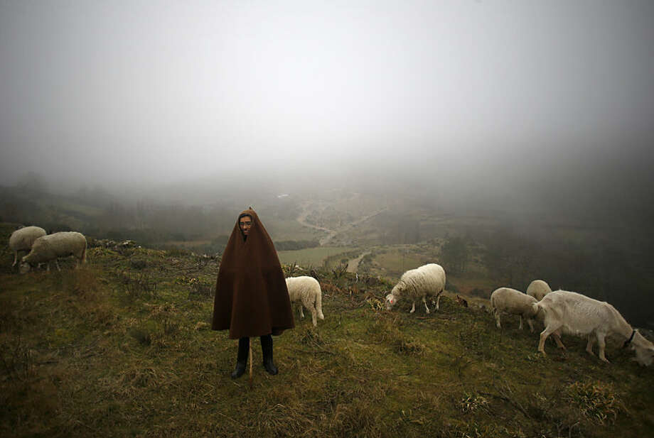"Portuguese shepherd Joaquina Martinho, 69, stands by her flock of goats and sheep as they eat fresh grass during a foggy evening on the mountains around Mazes village, near Lazarim, northeaster Portugal, Monday, Feb. 16, 2015. Local women wear a traditional cape or ""capucho"" made of wool weave that helps them to shelter against the cold and rainy weather conditions. (AP Photo/Francisco Seco)"