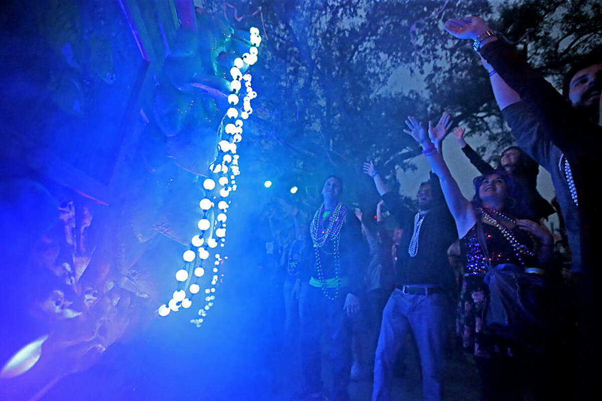Revelers cheer for beads though clouds of theatrical smoke from a float during the Krewe of Proteus Mardi Gras parade in New Orleans, Monday, Feb. 16, 2015. The day is known as Lundi Gras, the day before Mardi Gras. (AP Photo/Gerald Herbert)