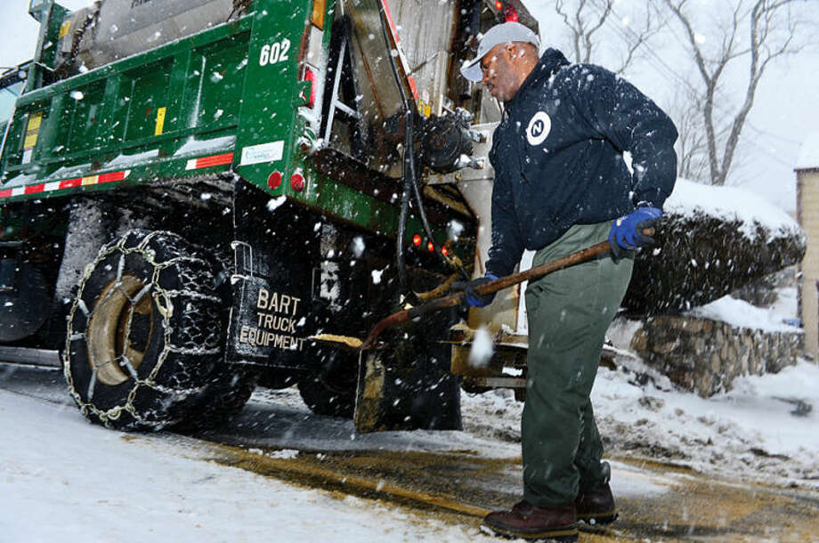 Hour photo / Erik Trautmann Norwalk DPW worker Phillip Senat frees his salt spreader while plowing area streets during the snowstorm Thursday morning.