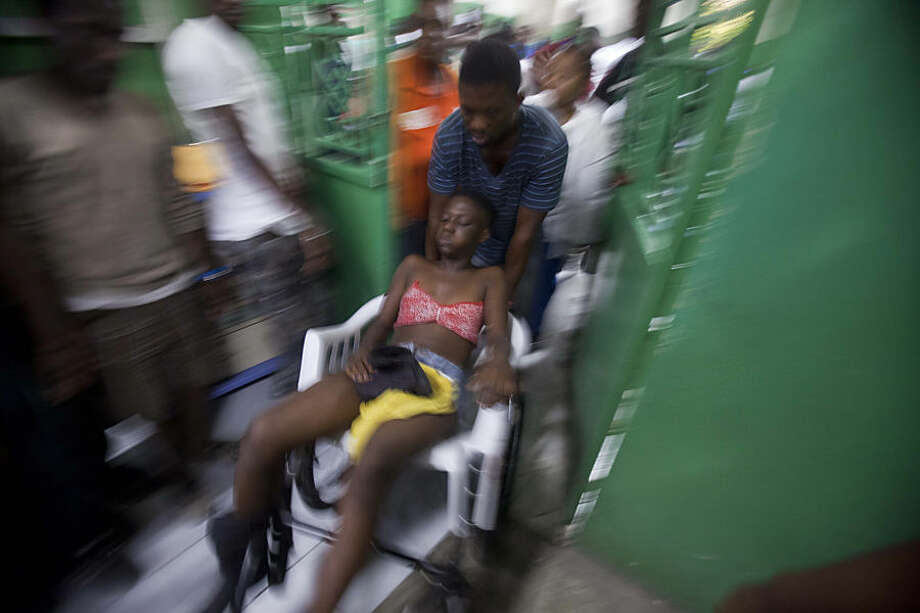 A reveler who was injured during carnival celebrations waits for treatment at the emergency room of the General Hospital in Port-au-Prince, Haiti, early Tuesday, Feb. 17, 2015. At least 20 people on a music group's packed Carnival float in the Haitian capital were killed Tuesday when they were electrocuted by a power line, officials said. The accident occurred as thousands of people filled the streets of downtown Port-au-Prince for the raucous annual celebration. People at the scene said someone on the float used a pole or stick to move a power line so the float could pass under it.( AP Photo/Dieu Nalio Chery)