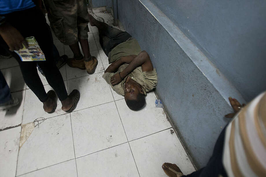 A man waits for treatment on the floor of the emergency room at the General Hospital in Port-au-Prince, Haiti, early Tuesday, Feb. 17, 2015. At least 20 people on a music group's packed Carnival float in the Haitian capital were killed Tuesday when they were electrocuted by a power line, officials said. The accident occurred as thousands of people filled the streets of downtown Port-au-Prince for the raucous annual celebration. People at the scene said someone on the float used a pole or stick to move a power line so the float could pass under it.( AP Photo/Dieu Nalio Chery)