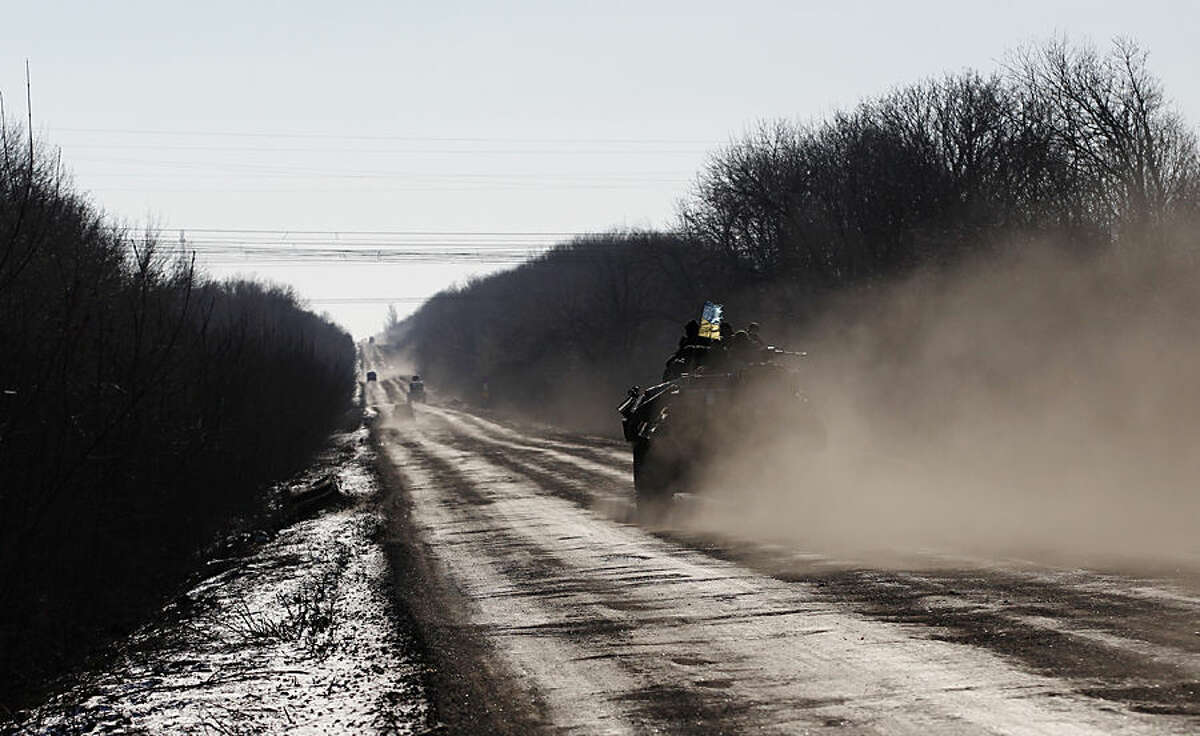 A Ukrainian armored vehicle passes on a road stretching away from the town of Artemivsk, Ukraine, towards Debaltseve, Tuesday, Feb. 17, 2015. Ukrainian government troops and Russia-backed rebels failed Tuesday to start pulling back heavy weaponry from the front line in eastern Ukraine as a deadline passed to do so. Under a cease-fire agreement negotiated by the leaders of Ukraine, Russia, Germany and France last week, the warring sides were to begin withdrawing heavy weapons from the front line on Tuesday. (AP Photo/Petr David Josek)