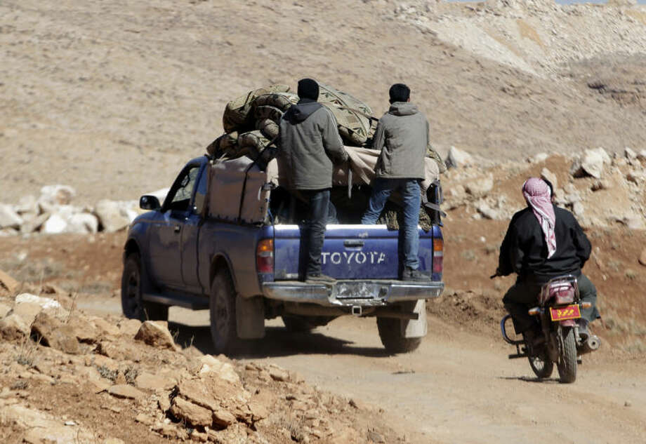 Syrian citizens ride in the back of a truck with their belongings after fleeing Yabroud, the last rebel stronghold in Syria's mountainous Qalamoun region, as they drive towards the Lebanese-Syrian border town of Arsal in eastern Lebanon, Thursday, Feb. 13, 2014. Syrian troops pounded Thursday the town of Yabroud the last rebel stronghold in Syria's mountainous Qalamoun region, forcing hundreds to flee into the nearby Lebanese town of Arsal. Backed by Lebanon's Hezbollah fighters, the Syrian army has been on a crushing offensive in the region since early December. (AP Photo/Bilal Hussein)