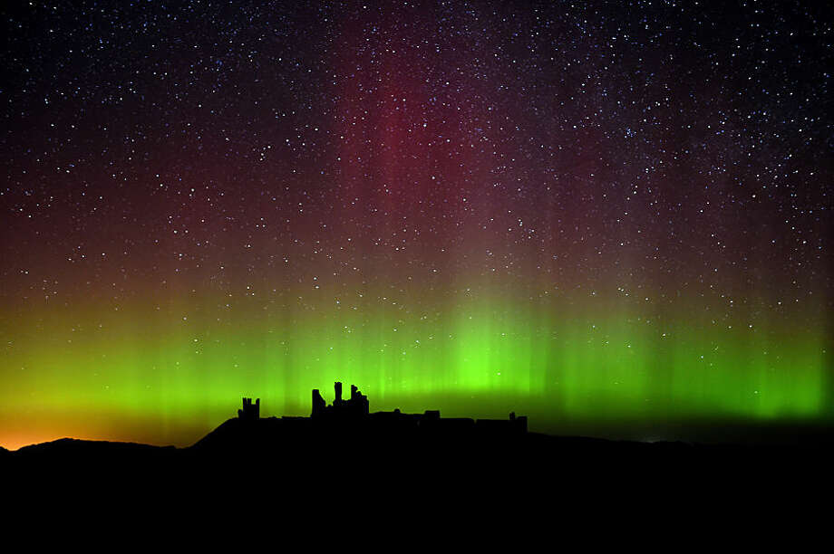 The aurora borealis, or the northern lights as they are commonly known are photographed, over Dunstanburgh Castle, in Northumberland, England, Tuesday Feb. 17, 2015. (AP Photo/PA, Owen Humphreys) UNITED KINGDOM OUT, NO SALES, NO ARCHIVE,