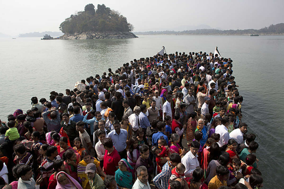 Indian devotees travel on a ferry to Umananda, left, a river island in the Brahmaputra that houses a Shiva temple, during Shivratri festival in Gauhati, India, Tuesday, Feb. 17, 2015. Shivratri, or the night of Shiva, is dedicated to the worship of Lord Shiva, the Hindu god of destruction. (AP Photo/Anupam Nath)