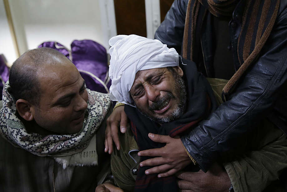 A man is comforted by others as he mourns over Egyptian Coptic Christians who were captured in Libya and killed by militants affiliated with the Islamic State group, outside of the Virgin Mary church in the village of el-Aour, near Minya, 220 kilometers (135 miles) south of Cairo, Egypt, Monday, Feb. 16, 2015. Egyptian warplanes struck Islamic State targets in Libya on Monday in swift retribution for the extremists' beheading of a group of Egyptian Christian hostages on a beach, shown in a grisly online video released hours earlier. (AP Photo/Hassan Ammar)