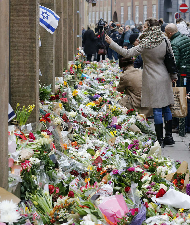 Flower tributes lay at the synagogue in Copenhagen, Denmark, Monday, Feb. 16, 2015. Denmark's Prime Minister Helle Thorning-Schmidt says she is mourning the two people killed and is vowing to protect freedom of speech along with Denmark's Jewish community. (AP Photo/Michael Probst)