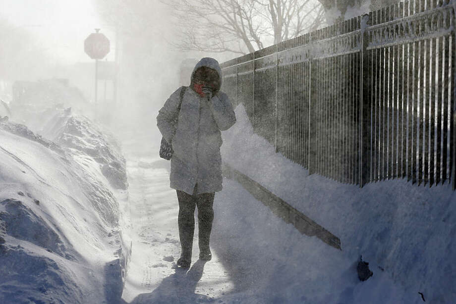A woman walks through blowing snow in the East Boston neighborhood of Boston, Monday, Feb. 16, 2015. New England remained bitterly cold Monday after the region's fourth winter storm in a month blew through. (AP Photo/Michael Dwyer)