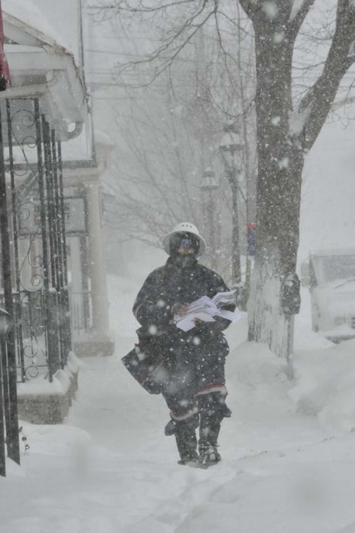 Mailman Simeon Reed makes his mail delivery rounds through deep snow and blizzard conditions on Broad Street in Bethlehem, Pa. on Thursday, Feb. 13, 2014. The storm spread heavy snow and sleet along the Northeast corridor. (AP Photo/Chris Post)