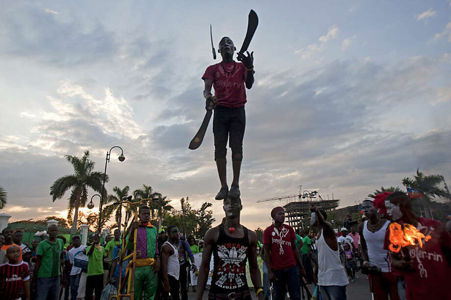 A performer juggles machetes while standing on the top of his partner's head, during Carnival celebrations in Port-au-Prince, Haiti, Monday, Feb. 16, 2015. (AP Photo/Dieu Nalio Chery)