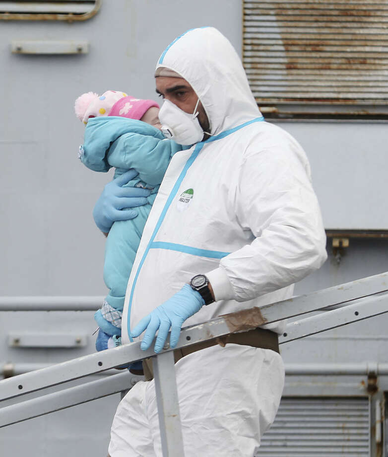 An Italian Navy officer carries a baby as migrants disembark from a tug boat after being rescued in Porto Empedocle, Sicily, southern Italy, Tuesday, Feb. 17, 2015. With Libya's security rapidly deteriorating, the number of migrants who set out in smugglers boats from Libyan shores toward Italy has surged. (AP Photo/Francesco Malavolta)