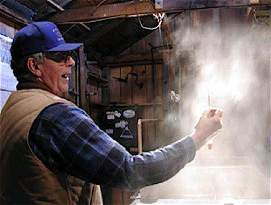 COURTESY OF RON WENZELRon Wenzel of the Wenzel Sugarhouse in Hebron tests the maple sap as it concentrates into syrup.