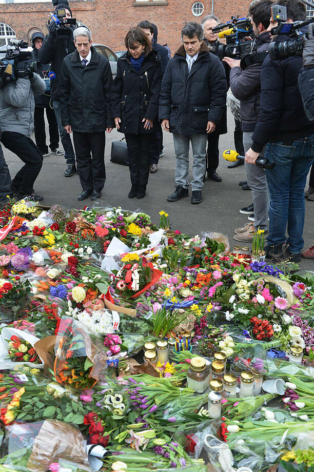 The Mayor of Paris, Anne Hidalgo , centre, looks at the floral tribute , as she visits the Teater Building 'Krudttonden', the scene of the first attack over the weekend, in Copenhagen, Monday, Feb. 16, 2015. The slain gunman suspected in the deadly Copenhagen attacks was a 22-year-old with a history of violence and Danish authorities say he may have been inspired by Islamic terrorists — and possibly the Charlie Hebdo massacre in Paris. (AP Photo/Polfoto, Mik Eskestad) DENMARK OUT