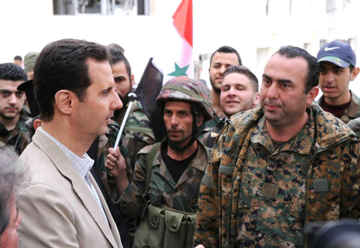 FILE - In this file photo taken on Sunday April 20, 2014 and released by the Syrian official news agency SANA, Syrian President Bashar Assad, left, talks to government soldiers during his visit to the Christian village of Maaloula, near Damascus, Syria. (SANA via AP, File)