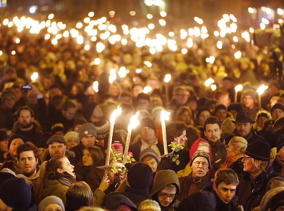 Hundreds of people gather for a vigil near the cultural club in Copenhagen, Denmark, Monday, Feb. 16, 2015. The slain gunman behind two deadly shooting attacks in Copenhagen was released from jail just two weeks ago and might have become radicalized there last summer, a source close to the Danish terror investigation told The Associated Press on Monday. The prime ministers of Denmark and Sweden were expected to join thousands of people at memorials in Copenhagen on Monday evening. (AP Photo/Michael Probst)