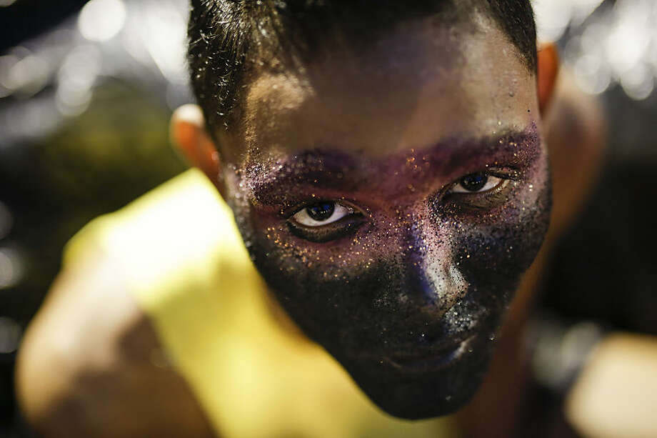 A reveler from the Sao Clemente samba school poses for a photo as he waits for the start of the Carnival parade at the Sambadrome in Rio de Janeiro, Brazil, Monday, Feb. 16, 2015. (AP Photo/Felipe Dana)