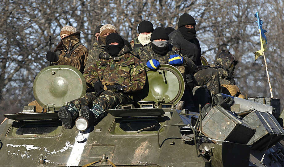 Ukrainian government soldiers sit on top of their armored vehicle driving on a road stretching away from the town of Artemivsk, Ukraine, towards Debaltseve, Tuesday, Feb. 17, 2015. Ukrainian government troops and Russia-backed rebels failed Tuesday to start pulling back heavy weaponry from the front line in eastern Ukraine as a deadline passed to do so. Under a cease-fire agreement negotiated by the leaders of Ukraine, Russia, Germany and France last week, the warring sides were to begin withdrawing heavy weapons from the front line on Tuesday. (AP Photo/Petr David Josek)