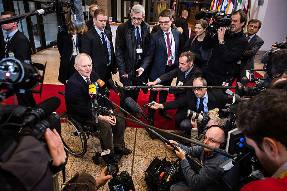 German Finance Minister Wolfgang Schaeuble, left, talks with journalists as he arrives for a meeting of Eurogroup finance ministers at the EU Council building in Brussels on Monday, Feb. 16, 2015. Greece's radical left government and its European creditors headed into new talks Monday on the debt-heavy country's stuttering bailout program, but expectations are low despite a fast-approaching deadline for some kind of deal. (AP Photo/Geert Vanden Wijngaert)