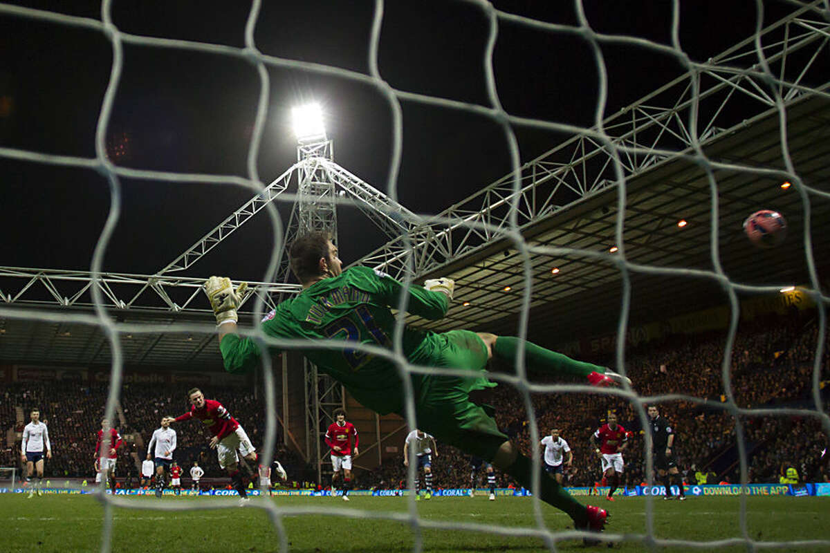 Manchester United's Wayne Rooney, lower centre left, scores a penalty past Preston goalkeeper Thosten Stuckmann during the English FA Cup Fifth Round soccer match between Preston and Manchester United at Deepdale Stadium in Preston, England, Monday Feb. 16, 2015. (AP Photo/Jon Super)