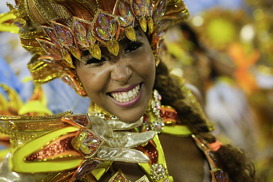A performer from the Portela samba school smiles during the Carnival parade at the Sambadrome in Rio de Janeiro, Brazil, Monday, Feb. 16, 2015. (AP Photo/Felipe Dana)