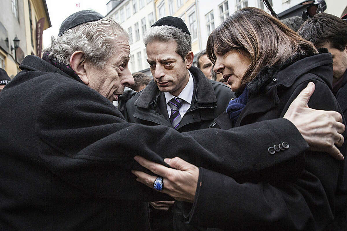 Former Chief Rabbi Bent Melchior, left, embraces Paris Mayor Anne Hidalgo with French Chief Rabbi Moise Lewin at centre, during a visit the Synagogue in Copenhagen, Monday, Feb. 16, 2015, after the attacks at the weekend. The slain gunman suspected in the deadly Copenhagen attacks was a 22-year-old with a history of violence and Danish authorities say he may have been inspired by Islamic terrorists - and possibly the Charlie Hebdo massacre in Paris. (AP Photo/Polfoto, Stine Bidstrup) DENMARK OUT
