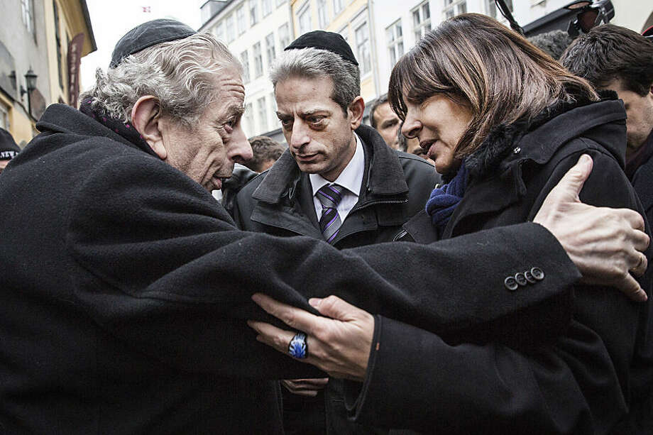 Former Chief Rabbi Bent Melchior, left, embraces Paris Mayor Anne Hidalgo with French Chief Rabbi Moise Lewin at centre, during a visit the Synagogue in Copenhagen, Monday, Feb. 16, 2015, after the attacks at the weekend. The slain gunman suspected in the deadly Copenhagen attacks was a 22-year-old with a history of violence and Danish authorities say he may have been inspired by Islamic terrorists — and possibly the Charlie Hebdo massacre in Paris. (AP Photo/Polfoto, Stine Bidstrup) DENMARK OUT