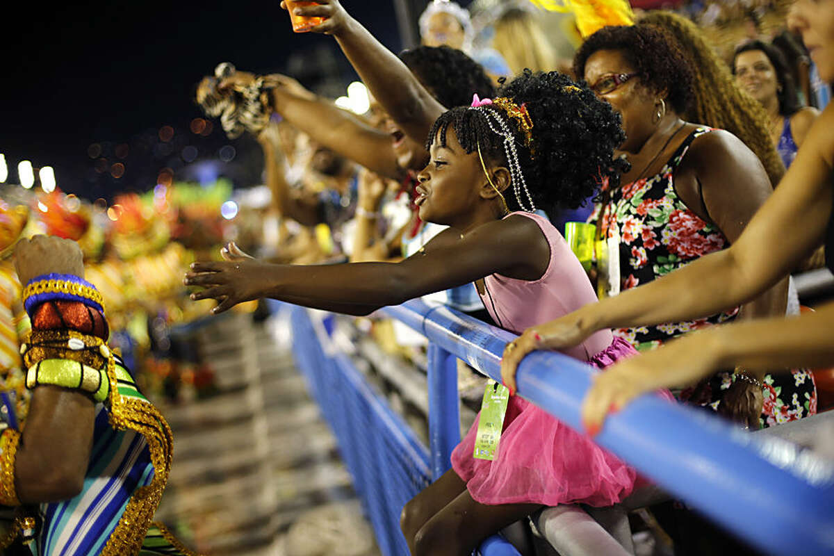 A child cheers Beija Flor samba school performers during the Carnival parade in the Sambadrome in Rio de Janeiro, Brazil, Tuesday, Feb. 17, 2015. (AP Photo/Silvia Izquierdo)