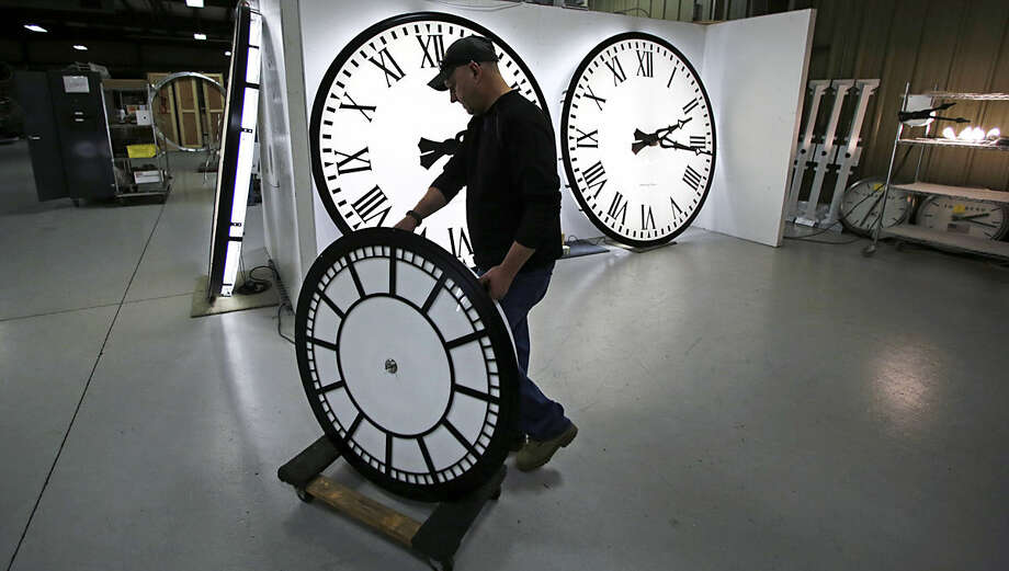 Dan LaMoore wheels a clock away from the test area as it is prepared to be shipped to a Tennessee school at the Electric Time Company in Medfield, Mass., Thursday, March 10, 2016. Most Americans will lose an hour of sleep this weekend, but gain an hour of evening light for months ahead, as Daylight Saving Time returns this weekend. The time change officially starts Sunday at 2 a.m. local time. (AP Photo/Charles Krupa)