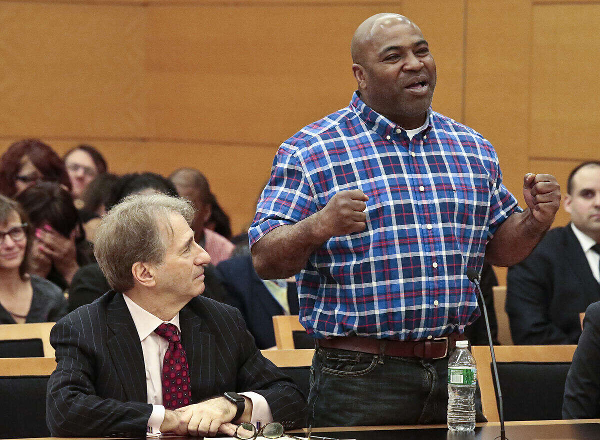 Andre Hatchett, right, stands next to his lawyer Barry Scheck, left, as he speaks about his faith in his innocence, during a hearing on his exoneration in court, Thursday March 10, 2016, in the Brooklyn borough of New York. Hatchett has been freed from prison and his conviction overturned Thursday after prosecutors and defense lawyers said a review of his case had found too many problems for it to stand. (AP Photo/Bebeto Matthews)