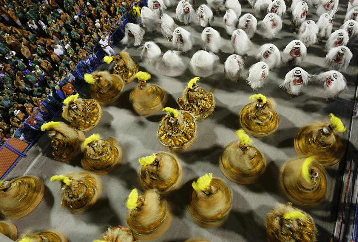 Performers from the Sao Clemente samba school file past spinning, in the Carnival parade at the Sambadrome in Rio de Janeiro, Brazil, Monday, Feb. 16, 2015. (AP Photo/Leo Correa)
