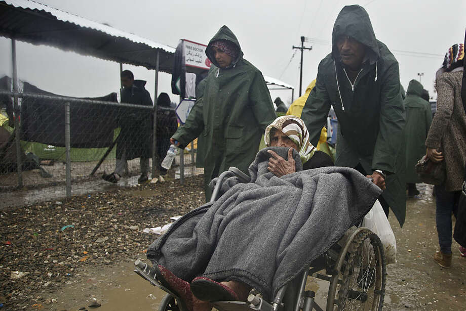A migrant old woman in a wheelchair is pushed at the Greek border camp near Idomeni, Thursday, March 10, 2016. After nearly three days of rain, conditions in the refugee camp on the Greek-Macedonian where about 14,000 people are stranded have deteriorated significantly, with many of its residents struggling to re-pitch their small camping tents in slightly drier patches. (AP Photo/Visar Kryeziu)