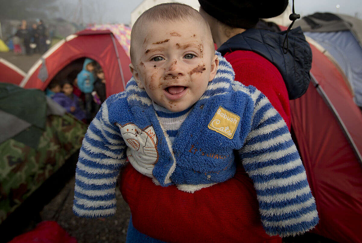 A child with chocolate stains on his face smiles in his mother's arm at the northern Greek border station of Idomeni, Friday, March 11, 2016. After nearly three days of rain, conditions in the refugee camp on the Greek-Macedonian where about 14,000 people are stranded have deteriorated significantly, with many of its residents struggling to re-pitch their small camping tents in slightly drier patches. (AP Photo/Vadim Ghirda)