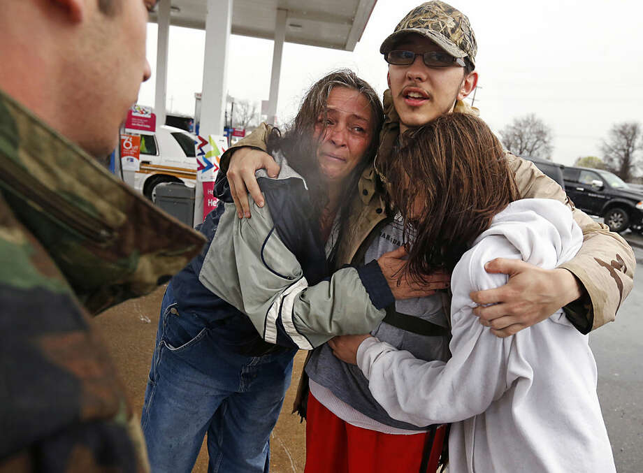 Dacia Winters, left, embraces Ryan Ficca, center, and Stormy Winters after they were evacuated in a Louisiana National Guard high water vehicle from rising floodwaters in Bossier Parish, La., Thursday, March 10, 2016. Heavy rain has forced evacuations and caused flash flooding for more than a day. (AP Photo/Gerald Herbert)